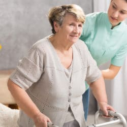 Senior woman with walking stick and her helpful carer