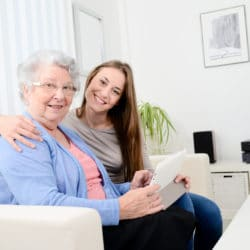 cheerful young girl sharing time with an old senior woman and teaching internet with computer tablet