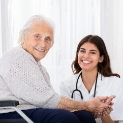 Portrait Of Happy Female Doctor With Disabled Senior Patient On Wheelchair In Hospital