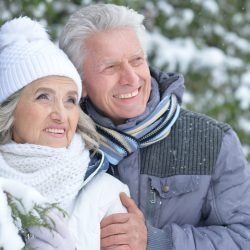 Portrait of happy senior couple having fun in winter park looking at the distance