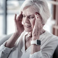 Sharp pain. Old female person keeping eyes closed and wrinkling forehead while touching temples