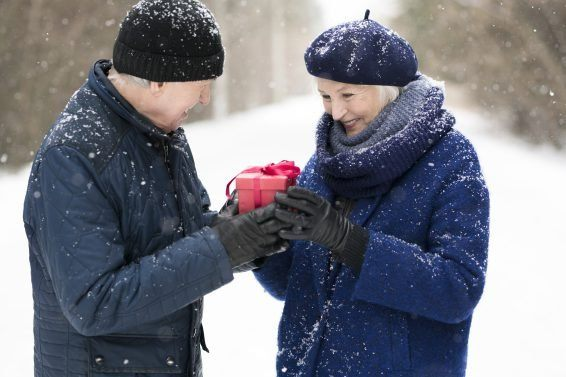 Waist up portrait of modern senior man giving present to smiling wife in snowy winter forest, copy space