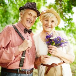 Smiling senior couple having rest in park on summer day
