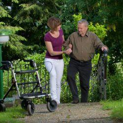 Senior mit Rollator und Pflegekraft