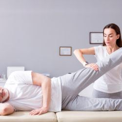 Personal treatment. Glad male patient lying down with female concentrated and serious physiotherapist performing some stretch exercises on mans leg