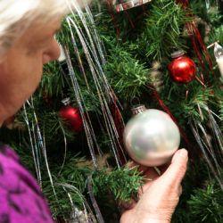 Seniorin schmückt künstlichen Weihnachtsbaum