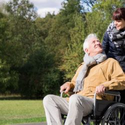 Photo of woman supporting elderly man on wheelchair