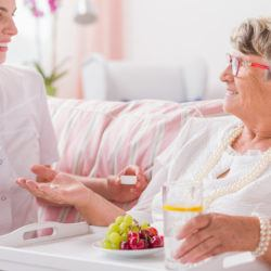 Senior woman taking her pills from young nurse sitting in front of her