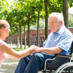 Happy Young Woman Holding Hands Of Her Disabled Father On Wheelchair In Park