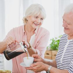 Senior woman pouring coffee for a man in the kitchen