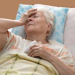 Sick senior woman lying at bed