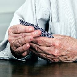 Close up of old man hands holding cards in game on table