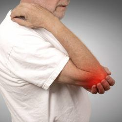 Closeup senior man with elbow inflammation colored in red suffering from pain and rheumatism isolated on gray wall background