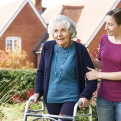 Daughter Helping Senior Mother To Use Walking Frame